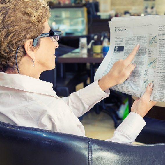 Symbolbild Frau liest Zeitung mit Vorlesesystem Orcam