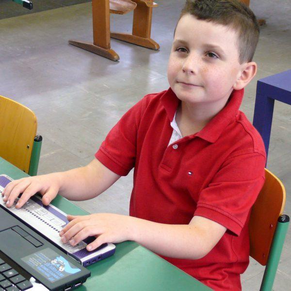 Symbolbild Kind in Grundschule mit Lesegerät
